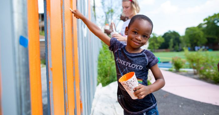 young boy painting Space to Grow schoolyard fence