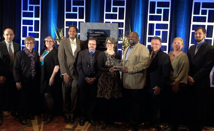 Partners of Space to Grow standing on stage with award, blue background
