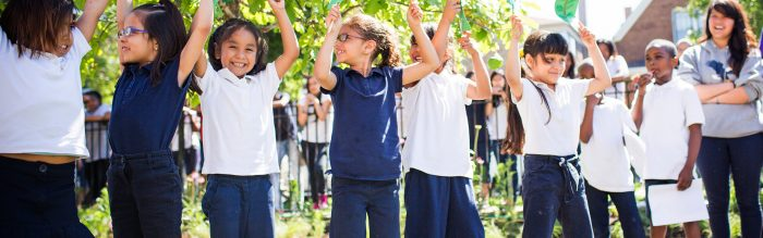 kids in white and blue school uniforms raising their hands outside