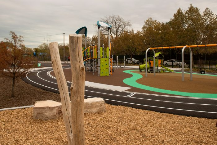 A schoolyard play structure, track and a tree structure.